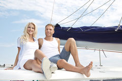 Attractive couple sitting on sailing boat - love. Stock Photos