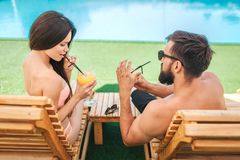 Attractive couple is sitting on sunbeds and drinking cocktails. Girl looks down. She holds straw. Guy wears glasses. Attractive couple is sitting on sunbeds and stock photography