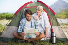 Attractive couple sitting by their tent reading map Stock Photography