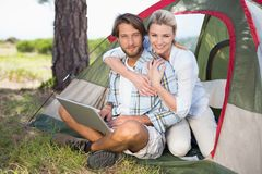 Attractive couple sitting by their tent using laptop smiling at camera Stock Photos