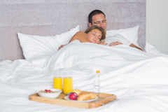 Attractive couple sleeping with breakfast tray on bed. At home in bedroom Royalty Free Stock Photography