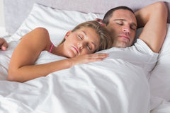 Attractive couple sleeping and cuddling in bed Stock Images