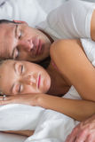 Attractive couple sleeping and spooning in bed Royalty Free Stock Images
