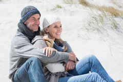 Attractive couple smiling on the beach in warm clothing Royalty Free Stock Image