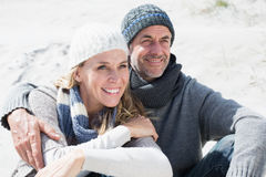Attractive couple smiling on the beach in warm clothing Royalty Free Stock Photo