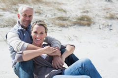 Attractive couple smiling at camera on the beach Stock Photography