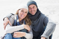 Attractive couple smiling at camera on the beach in warm clothing Stock Photo
