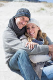 Attractive couple smiling at camera on the beach in warm clothing Royalty Free Stock Image