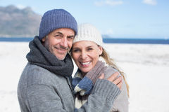Attractive couple smiling at camera on the beach in warm clothing Royalty Free Stock Images