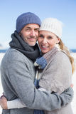 Attractive couple smiling at camera on the beach in warm clothing Royalty Free Stock Photo