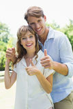 Attractive couple smiling at camera and showing thumbs up in the park Stock Images