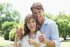 Attractive couple smiling at camera and showing thumbs up in the park Royalty Free Stock Photo