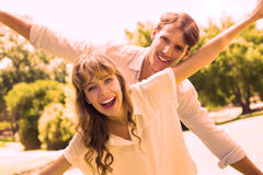 Attractive couple smiling at camera and spreading arms in the park Stock Image