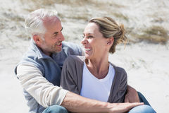 Attractive couple smiling at each other on the beach Royalty Free Stock Image