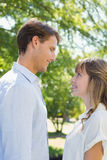 Attractive couple smiling at each other in the park Stock Photos