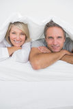 Attractive couple smiling under the covers at the camera Royalty Free Stock Photo