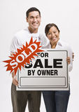 Attractive couple with sold sign Stock Image