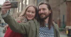 Young beautiful couple taking selfie in a city. stock footage