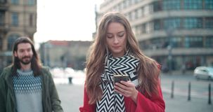 Young woman waiting for her boyfriend and typing on phone. Attractive couple spending day together in a city. Concept of technology and relationship Stock Photos