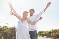 Attractive couple standing with arms raised by the road Royalty Free Stock Photo