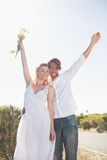 Attractive couple standing with arms raised by the road Royalty Free Stock Photography