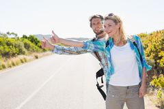 Attractive couple standing on the road hitch hiking Stock Photography