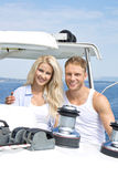 Attractive couple standing on sailing boat - sailing trip. Royalty Free Stock Images