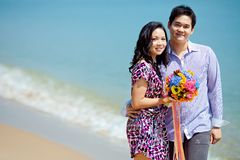 Attractive couple standing together on the beach Royalty Free Stock Photos