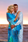 Attractive couple at sunset. Young couple in love near the sea at sunset Royalty Free Stock Images