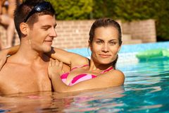 Attractive couple in swimming pool smiling Stock Images
