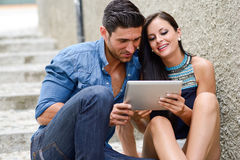 Attractive couple with tablet computer in urban background Royalty Free Stock Photo