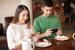 Attractive couple taking pictures of their food Royalty Free Stock Photo