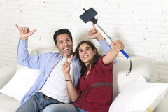 Attractive couple taking selfie photo or shooting self video with mobile phone and stick sitting at home couch smiling happy Royalty Free Stock Photos