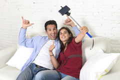 Attractive couple taking selfie photo or shooting self video with mobile phone and stick sitting at home couch smiling happy Stock Photography