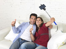 Attractive couple taking selfie photo or shooting self video with mobile phone and stick sitting at home couch smiling happy Royalty Free Stock Image