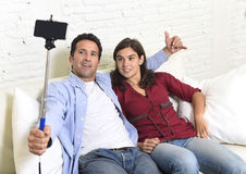 Attractive couple taking selfie photo or shooting self video with mobile phone and stick sitting at home couch smiling happy. Young attractive couple taking Stock Image