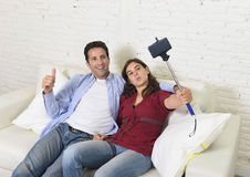 Attractive couple taking selfie photo or shooting self video with mobile phone and stick sitting at home couch smiling happy. Young attractive couple taking Royalty Free Stock Photography