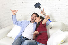 Attractive couple taking selfie photo or shooting self video with mobile phone and stick sitting at home couch smiling happy. Young attractive couple taking Stock Photo