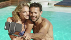 Attractive couple taking selfie by the pool. On a sunny day stock video