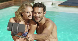 Attractive couple taking selfie by the pool. On a sunny day stock video footage