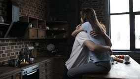 Attractive couple tenderly embracing in kitchen stock footage