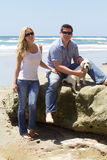 Attractive Couple with their Labrador Retriever Puppy at the Beach Royalty Free Stock Photo