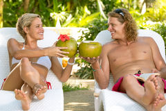Attractive couple toasting with coconut Stock Photo