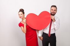 Attractive couple toothy smile, look out from behind big heart. Indoor, studio shot,  on gray background Stock Photos