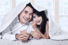 Attractive couple under blanket Royalty Free Stock Photos