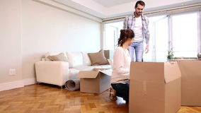 Attractive couple unpacking boxes in their living room stock footage