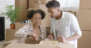 Attractive couple unpacking their things in new home stock footage