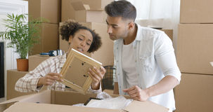 Attractive couple unpacking their things in new home Royalty Free Stock Photos