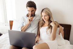Attractive couple using laptop in bedroom. Royalty Free Stock Photos