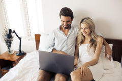 Attractive couple using laptop in bedroom. Royalty Free Stock Image